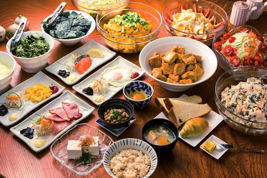 自社農園の米や野菜、卵を使った朝食メニュー。中央の生卵や目玉焼き、サケの塩焼き、スクランブルエッグ、ベーコンなどは追加メニュー