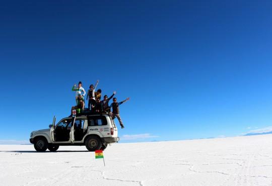ウユニ塩湖で、ボリビアの国旗と共に記念撮影