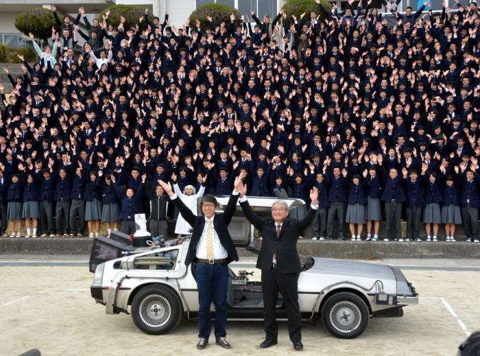 デロリアンを披露した錦江湾高校OBの岩元美智彦さん(手前左)。後輩たちと笑顔で記念撮影した