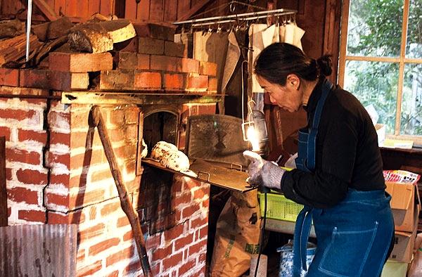 窯でのパン焼きは薪割りも含めかなり重労働。焼くのは火曜と木曜の週2回。川辺やすらぎの郷、鹿児島市の地球畑などでも販売