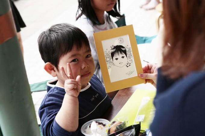 似顔絵を描いてもらって嬉しそうな男の子