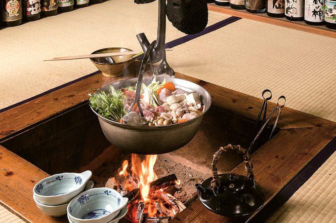 囲炉裏を囲んで食事を楽しむ