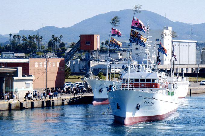 大漁旗を掲げて出港する漁船