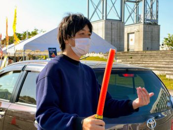 誘導棒を手に車を案内する井上正樹さん