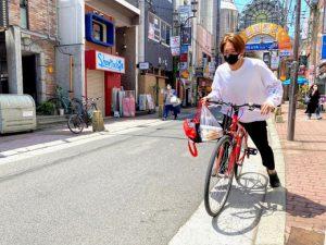 テイクアウト弁当をもって、自転車で配達に向かう店員