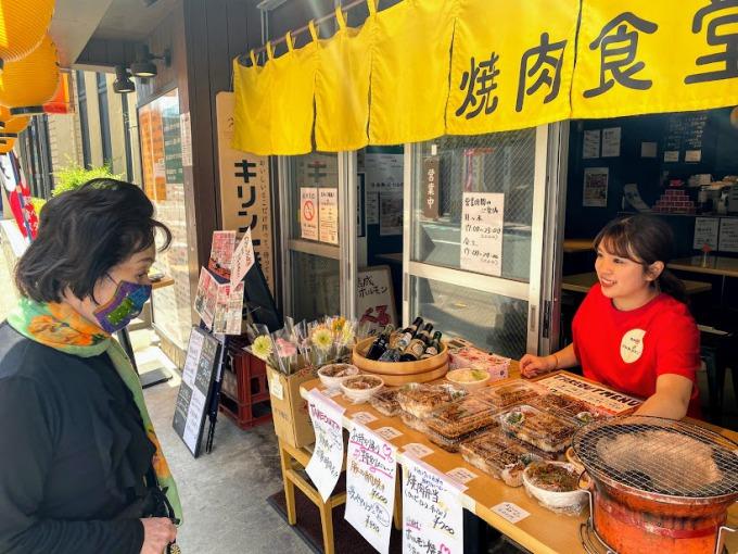 笑顔でテイクアウト弁当を販売する松本絵理香さん=鹿児島市千日町