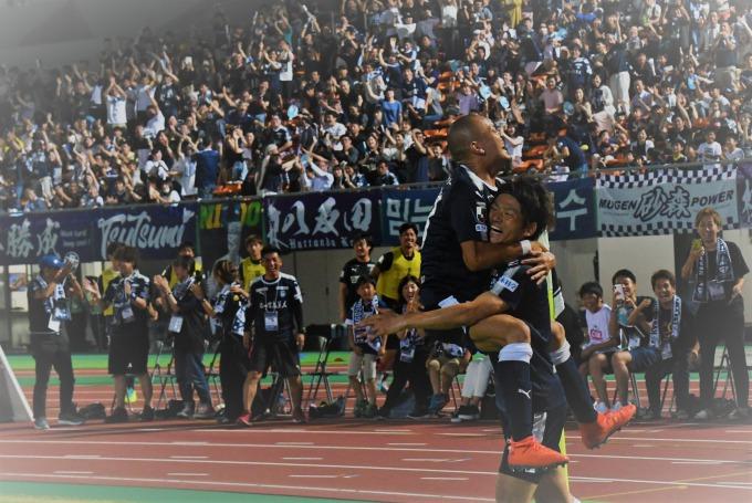 鹿児島ユナイテッドFC結成時からチームを支えるメンバー。赤尾の3季ぶりのゴールを一番に喜ぶ田上=白波スタジアム