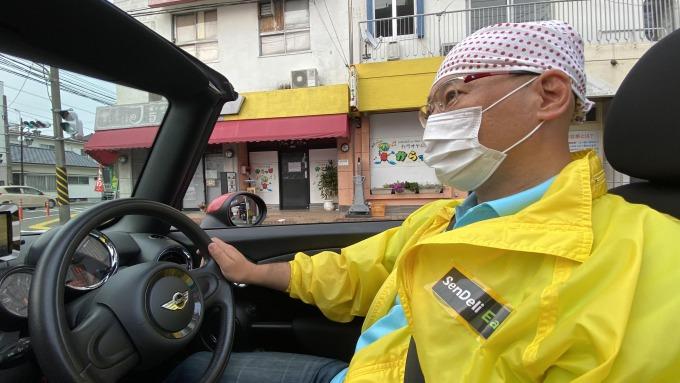 真っ赤なオープンカーで配達先に向かうボランティアの平田宗嗣さん