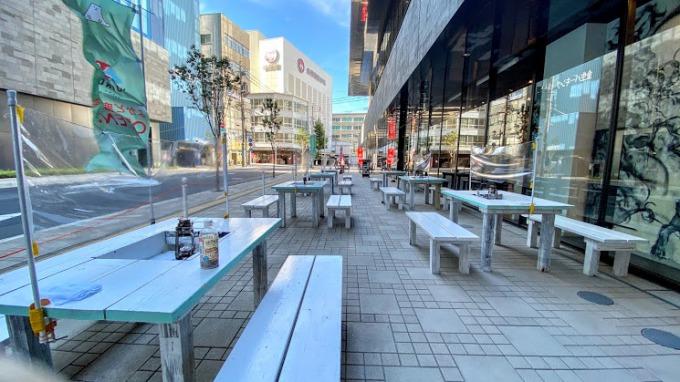 鹿児島銀行本店別館ビル前の敷地内歩道に登場した「よかどビアテラス」。テーブルには飛まつ防止用のビニールシートが設けられている