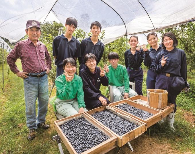 実習に協力するブルーベリー農家の向井邦雄さん(左)と曽於高校の生徒たち
